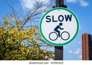 Round Sign on a Pole along a Bicycle Path Telling Cyclist to Slow Down