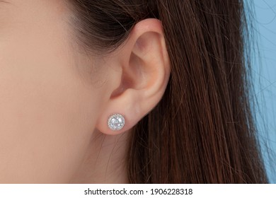 Round silver earrings on the ear of a well-groomed lady on a blue background