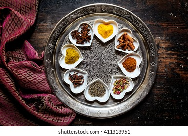 Round silver platter besides silk scarf on table holds eight white heart shaped trays with a variety of colorful spices