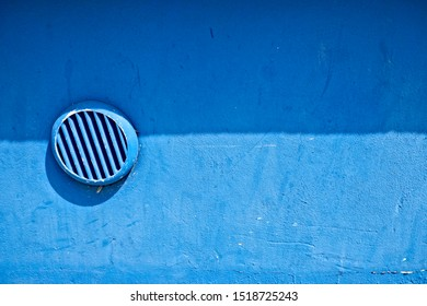 Round slatted vent port on an empty blue wall in two blue tones, abstract architecture detail.