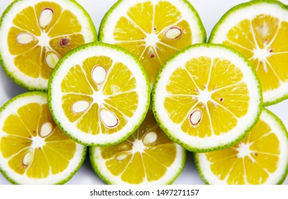 round slices of natural lime lemon with seeds on a white a background