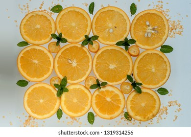 Round slices of oranges with mint leaves on the black, white, orange background