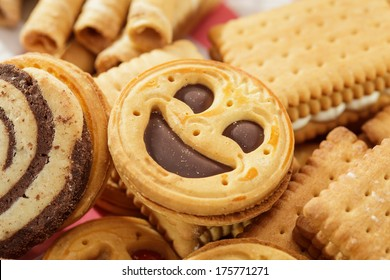 Round smiling chocolate cookie on a pile of biscuits