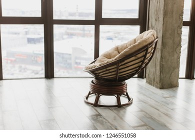 Round soft rocking chair stands in a penthouse loggia by the panaramny window