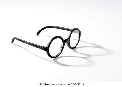 Round spectacles with shadow lying against white background