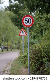 Round speed limit road sign on the road. 50 km per hour.