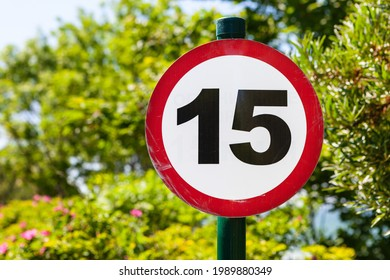 Round speed limit sign fifteen on the background of trees.