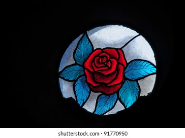 Round stained glass window of red rose