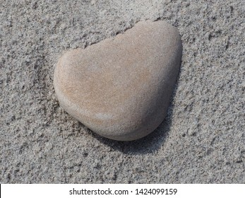 round stone in the Sand at the beach