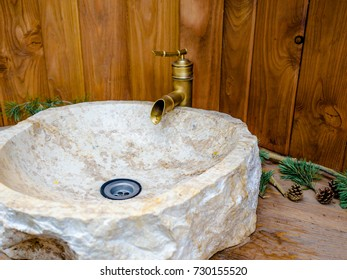 Round stone-like basin in the modern bathroom with brass tap water, Beautiful faucet and marble sink with wooden wall.