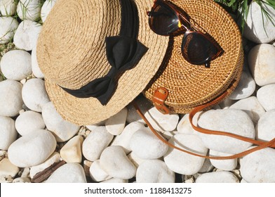 Round straw bag and straw hat with black sunglasses on pebble stones