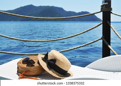 Round straw bag and straw hat with black sunglasses on a plastic lounge chair on a pier with sea, mountains and blue sky