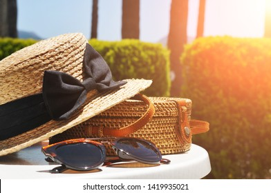 Round straw bag, straw hat and black sunglasses with green bushes and blue sky on the background with sunlight