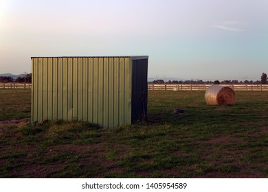 Round straw bale and horse shelter at sunset in Garfield, rural Victoria, Australia.