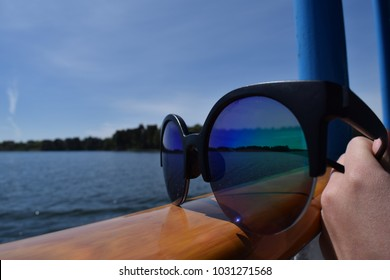 Round sunglasses with mirror of landscape on ship hand-rail. Close up view.