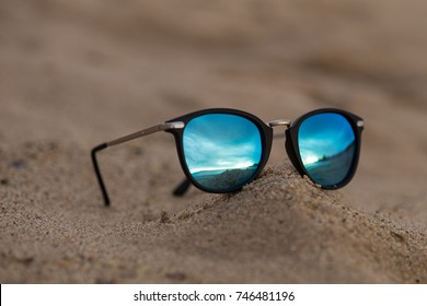 0ad62df488 Round sunglasses with mirror reflection on the sand on sunny summer beach. Travel  vacations concept
