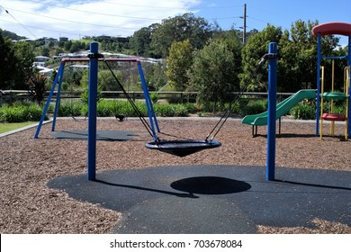 Round swing in kids park. Round swing attached with ropes to two metal posts or pillars in park. Rubber and Fragments of wood is laid as surface of the park.