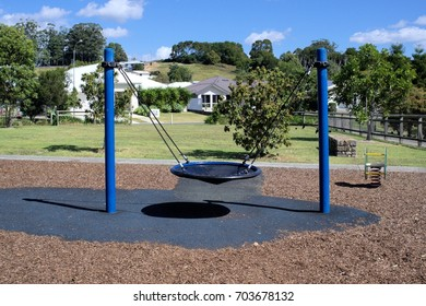 Round swing in kids park. Round swing attached with ropes to two metal posts or pillars in park. Rubber surface and fragments of wood are laid as surface of the park.