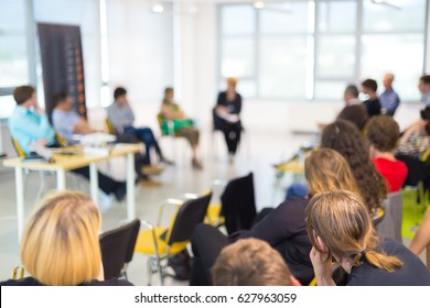 Round table discussion at business and entrepreneurship symposium. Audience in conference hall. Lens focus on unrecognized participant in rear of audience.