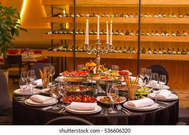 Round table with Italian food, black cloth, candelabra in the restaurant