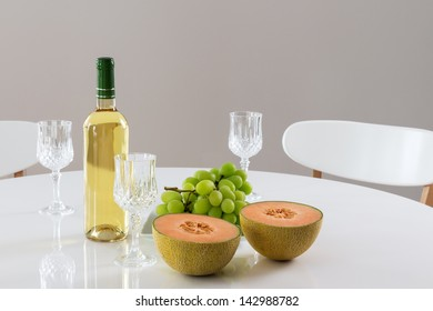 Round table with white wine, melon and green grapes.