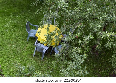 Round table with yellow tablecloth and blue chairs in a garden