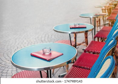 Round tables with chairs of traditional outdoor French cafe in Paris ready for service