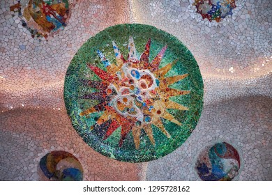 Round tile mosaic with sun on ceiling in the hall of hundred columns in the Barcelona Park Guell. False capstone.