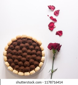 Round tiramisu cake on white table. cacao powder and decorated with fresh flowers. Italian classic dessert so sweet and delicious.