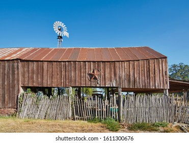 Round Top, Tx, USA - 20th September 2011: An old Wooden lean to barn with a rusty Tin roof, and the star of Texas hung on its wall on a street in Round Top, Texas.