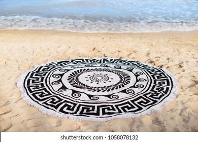 a round towel lies on the sand by the sea