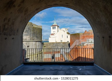 The round tower and old harbour masters house in Old Portsmouth, Portsmouth UK framed by an archway