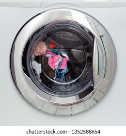 Round transparent door hatch automatic washing machine, through which you can see the washing of colored linen.