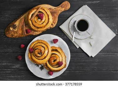 Round twisted Denish Buns with berries raspberries, syrup, white cup espresso coffee, sugar cubes, cinnamon sticks, star anise, cutting board made of wood olive on a black wooden background, top view