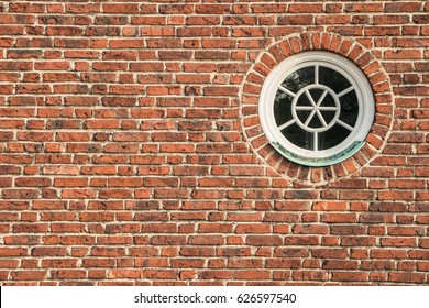 Round and vintage wooden window on brick wall. White window on red brick wall. Background of old red vintage brick wall and window. Abstract orange-red brick wall pattern. Filled full frame picture.