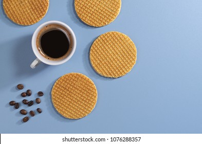 Round wafers and cup of coffee on blue table, top view