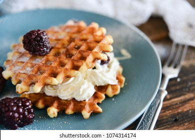 Round waffles with fresh blackberries and whipped cream, on natural wooden background in rustic style