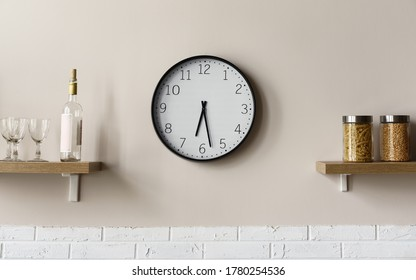 Round wall clock between wooden kitchen shelves