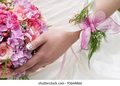 round wedding bouquet of pink flowers at girls hand