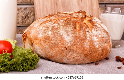 Round well-toasted bread lying on the tablecloth. Homemade bread. A bottle of milk, a cup of milk, greens, rough homemade tablecloth.