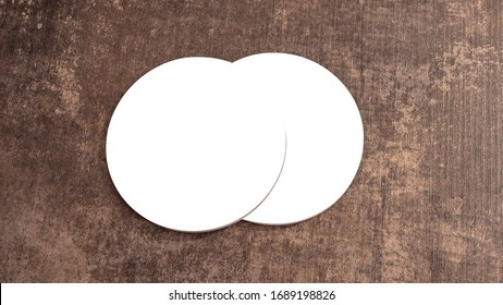 Round white blank drink coasters lying on the wooden table. Mock Up. Circular beer mat to protect the surface of a table. Top View