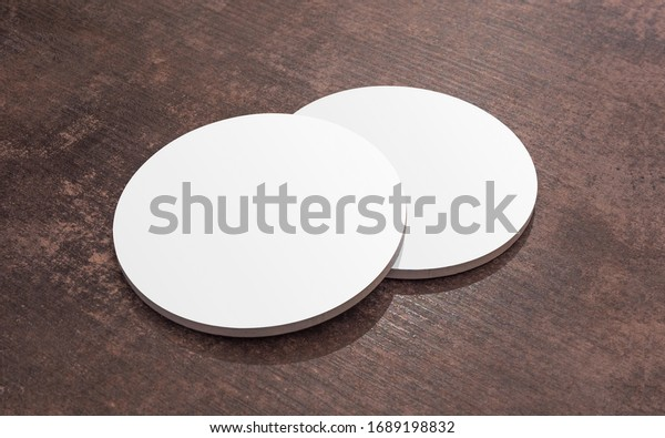 Round white blank drink coasters lying on the wooden table. Mock Up. Circular beer mat to protect the surface of a table.