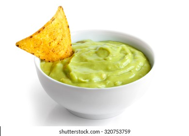 Round white bowl of guacamole dip isolated in perspective. Tortilla chip in dip.