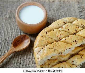 Round white bread. Milk in wooden utensils