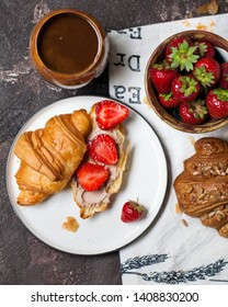 Round white flat plate with a croissant cut in half  with chocolate paste and fresh strawberries. Napkin, a сup of coffee, a сup of strawberries on a brown textured background.