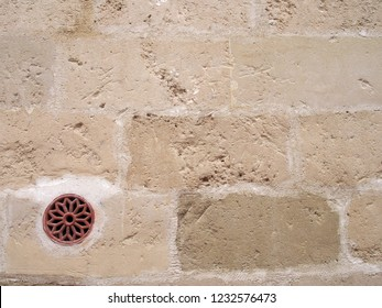 a round white flower shaped air vent in an old white stone wall