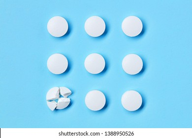 Round white medical pills arranged in square order and one of them is crushed into four parts. Pill splitting.