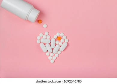 round  white pills  lined in the shape of a heart  poured out on a pink background of white plastic pill bottle. dietary supplements.  additive to nutrition. biohacking