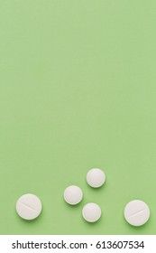 Round white pills on green color background