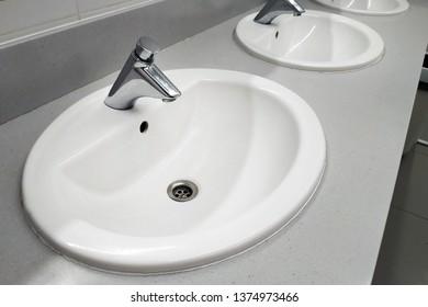Round white washbasins in public toilet. Chrome-plated pressure washbasin mixer